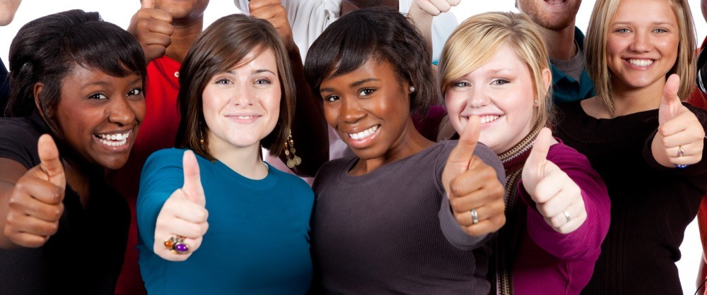 Several women college students stand together holding their thumbs up with pride. photo/Adobestock