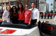 Five people sitting on back of convertible car facing forward. Katie Dew on left, UC Provost Beverly Davenport, two members of UC's engineering ACM-W women's group and UC President Santa Ono on right.