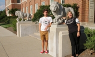 Diane Dew stands with her son Austin near the lions Mick and Mack in front of McMicken Hall/2014. photo/Melanie T-Schefft