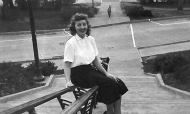Jean Michel sits on railing along steps in front of McMicken Hall in 1950.