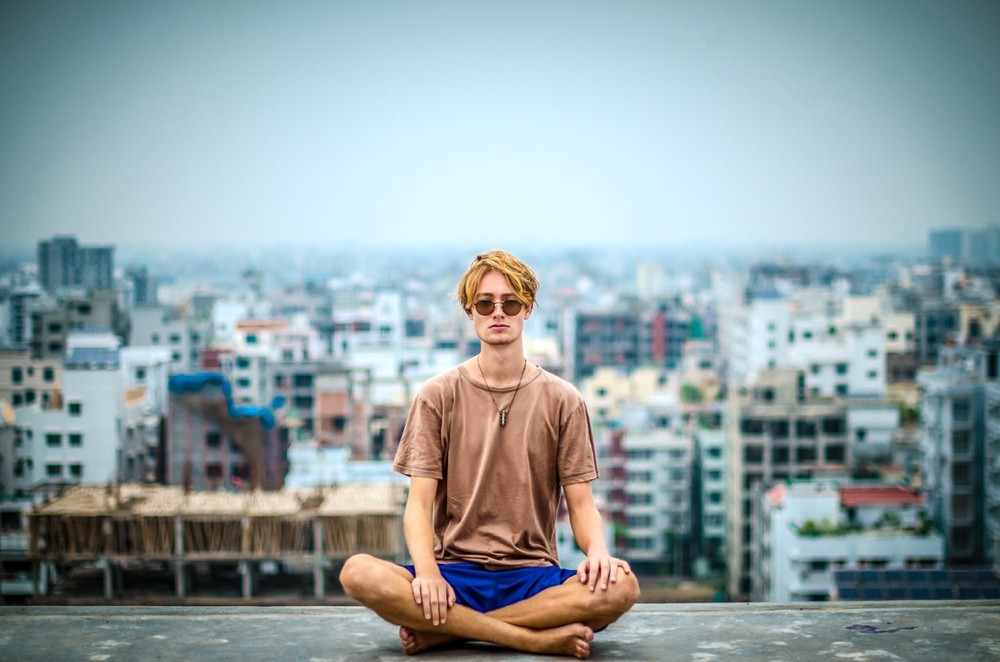 Young man sitting in yoga pose on an ocean beach. photo/Isabell Winter/Upsplash