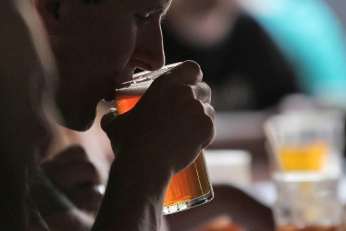 Young man sips a drink of beer. photo/Robert Mathews/Upsplash