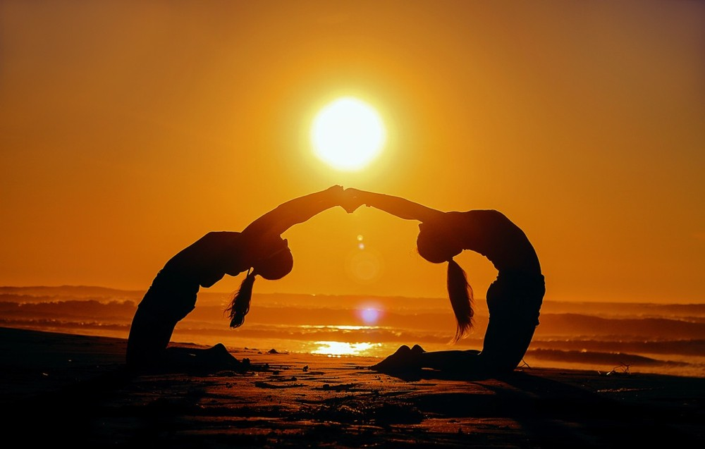 Two young women do yoga stretches together on an ocean beach at sunset. photo/Aziz Acharki/Upsplash