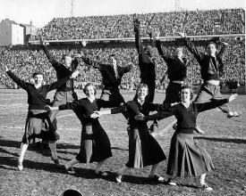 Cheerleaders in 1950s with Bearcat mascot.