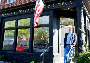 University of Cincinnati alum and an architect, Mike Watkins, stands in front of his storefront office.