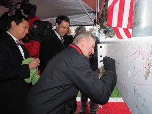 UC officials sign a piece of steal before it is raised up at Nippert Stadium.
