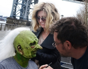 """University of Cincinnati alum Cara Sullivan is shown working on the crazy white hair of an actor in costume for the television show """"Saturday Night Live."""""""