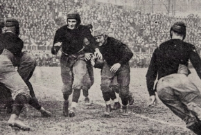 "A vintage photo of the University of Cincinnati football team running a play with ""original Bearcat"" Teddy Baehr with the ball."