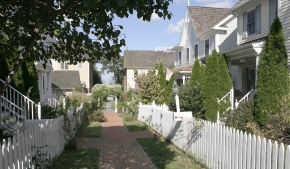 A beautiful brick walkway wanders between two white picket fences, in a walkable community designed by Mike Watkins.