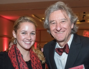 A photo of a smiling young woman, Olivia Hiles, who is a University of Cincinnati student and the winner of a design contest. She is pictured with a University of Cincinnati dean, Robert Probst.