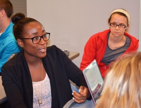 One of the University of Cincinnati Foundation board members sits and observes a classroom with students.