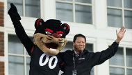 The University of Cincinnati president Santa Ono and the UC costumed mascot, the Bearcat, stand atop the football stadium -- arms upstretched in triumph.
