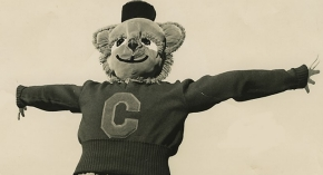 A vintage photograph of a 1950s University of Cincinnati costumed mascot, the Bearcat, leaps mid-air with arms outstretched.