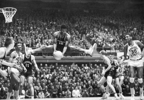 UC basketball great Oscar Robertson is shown with legs in a mid-air split -- an iconic Robertson pose.