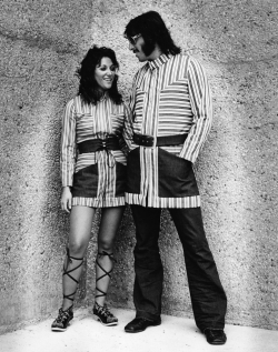 A couple in outlandish outfits, miniskirts and bell bottoms from the Seventies
