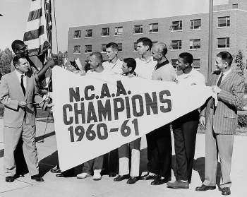 The winning UC basketball coach and team hold up an oversized pennant declaring UC as the NCAA Champions for 1960-61.