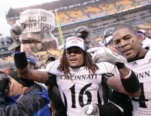 UC football players hold up a front page of the Cincinnati Enquirer declaring the team Big East champs in 2009.