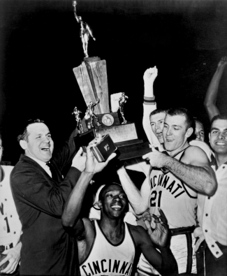 The UC basketball team and coach Ed Jucker hoist the 1961 trophy.