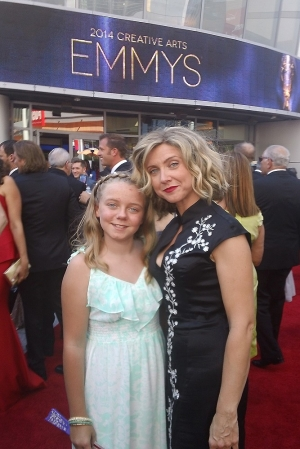 Alumna Cara Sullivan and her look-alike 11-year-old daughter Rachel stand in front of the Emmy Awards sign.