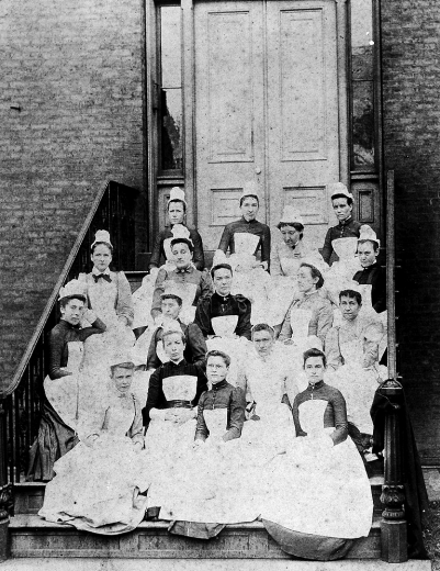 A vintage photograph of a group of student nurses sitting on a stoop -- the UC College of Nursing's 1891 class.