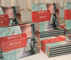 A stack of books -- the 125th Anniversary of the University of Cincinnati's College of Nursing.
