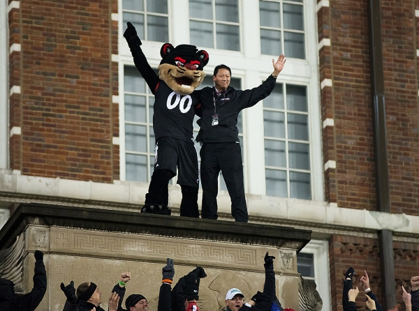 The University of Cincinnati Bearcat mascot and the UC president Santa Ono stand atop the football stadium after being lifted there by the fans.