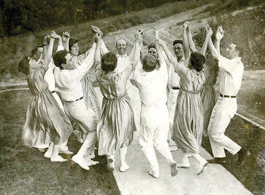 A 1916 black-and-white photograph of dancers in a circle, holding hands, and lifting their hands up in celebration of William Shakespeare's death 300 years before.