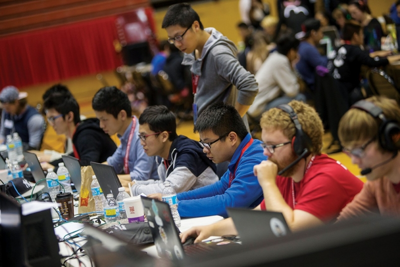 A long line of gamers engrossed in their screens during a UC gaming convention.