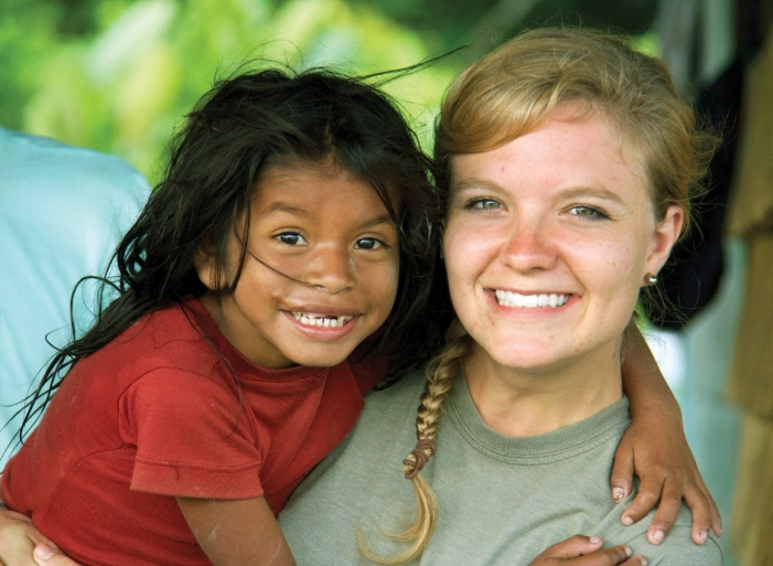 UC student Natalie Bullock gets a big hug from a girl from Warao while on her international travels.
