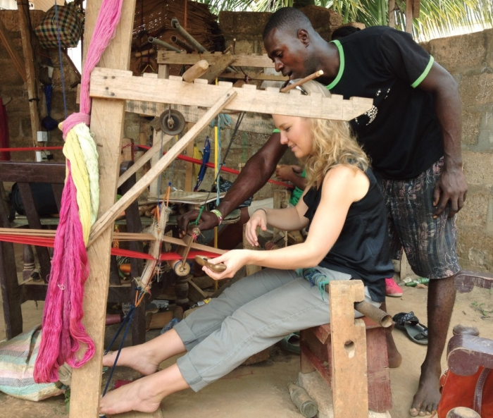 UC alumna Natalie Bullock, Bus '15, receives a lesson in weaving traditional Kente cloth during a trip to Ghana.