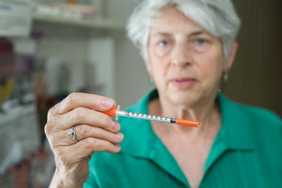 Dr. Judith Feinberg, a University of Cincinnati physician, holds a syringe.
