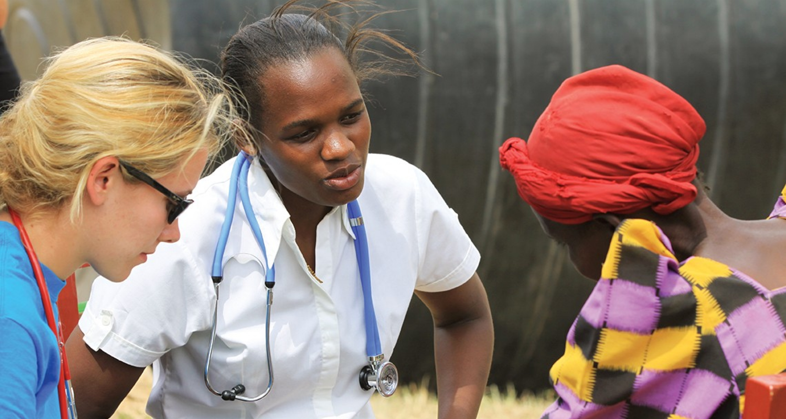 Maria Nakafeero (center) consults with a patient in Uganda. The UC graduate is now a research assistant with Global Health Uganda.