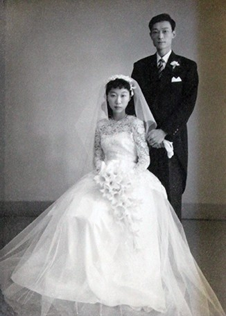 A black-and-white wedding photo with a bride seated and the groom standing behind. It shows UC President Santa Ono's parents, Takashi and Sachiko Ono, on their wedding day.