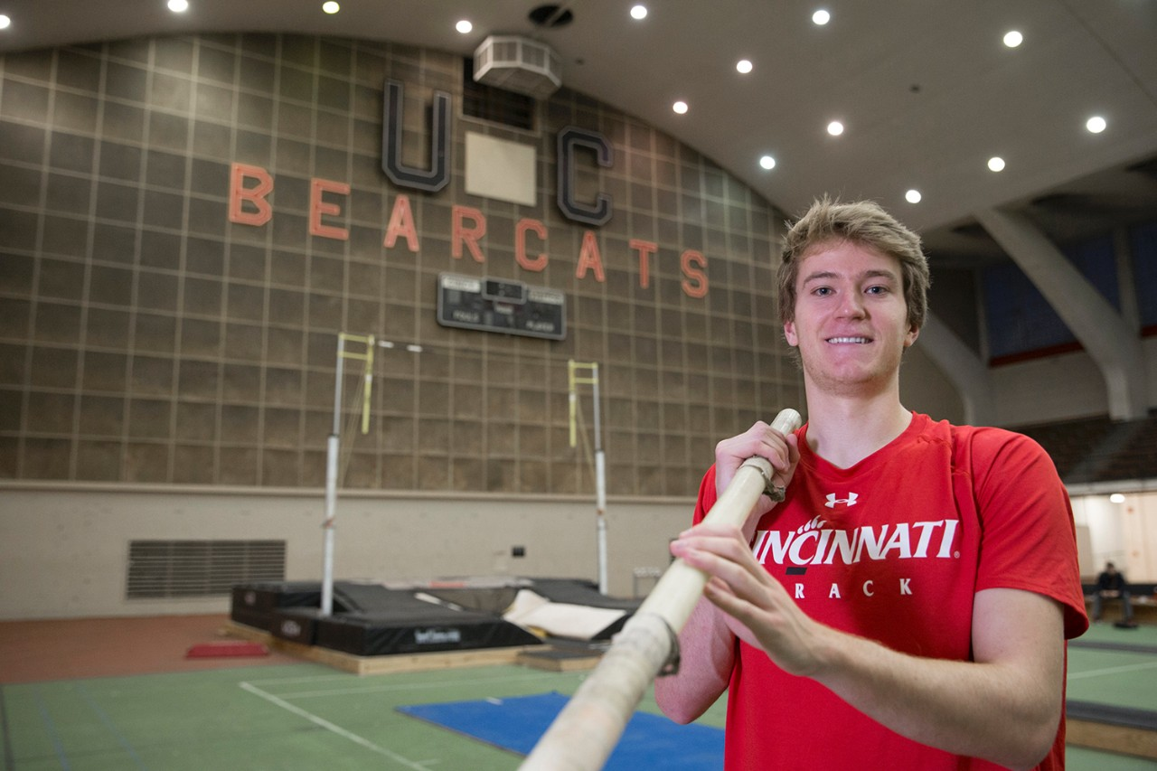 Adrian Valles holds pole vault inside UC's Armory Fieldhouse