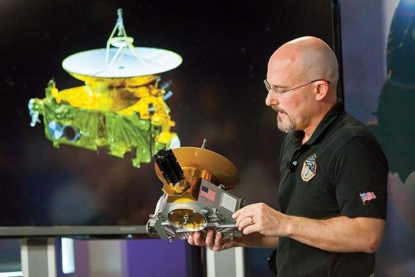 Chris Herman holds model of New Horizons space probe