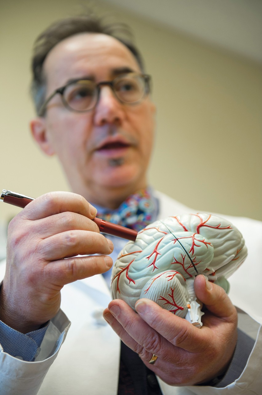Dr. Privitera holding a model of a human brain.