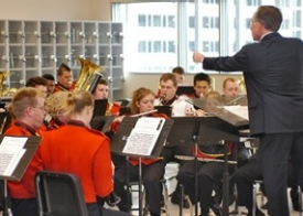 Terren Frenz directs the UC Bearcat Band at the dedication of the group's first official band room. Along the back wall are secure cages for instruments. The window faces Gettler Stadium