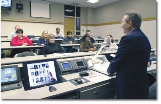 Malcolm Montgomery, at the document camera, shows how professors can greet students by name on their first day using illustrated online class lists. To the electronic classroom planner's left are a touch screen to control AV equipment, a built-in PC screen and two small monitors for far-site and near-site video (See near-site monitor, upper left). A distance learning camera and a far-site video screen are also visible in this College of Business classroom. photo/Lisa Ventre