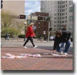 """""""Eat me,"""" pled the pre-packaged cupcakes placed on a busy downtown street by DAAP students who waited for public reactions. The passerby above accepts the invitation."""