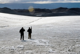 Researcher Scott Travis, left, and Colby Smith, geology graduate student, hike down the Istorvet Ice Cap in Greenland, one of many exotic locations where Lowell and his team study glacial patterns and their relation to climate change.