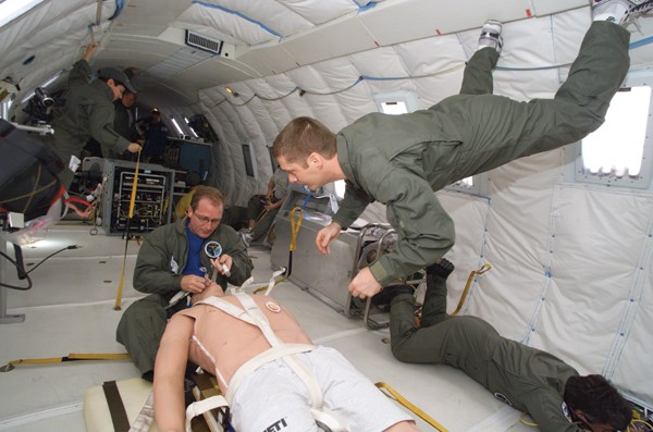 Riding in a DC-9 that the National Aeronautics and Space Administration uses to simulate weightlessness, UC surgeon Timothy Broderick floats above a patient mannequin while testing surgical robotic technologies that may eventually be used to treat injured soldiers during transport or even sick astronauts in space.