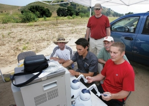 Assistant professor of surgery Timothy Broderick (far right), medical director for UC's Center for Surgical Innovation, and his team perform robotic telesurgery in a desolate valley in California on a simulated patient five miles away. In 2005, Dr. Broderick and his UC team used the da Vinci surgical robot to lead the nation's first live telesurgery from Ohio to California.  Photo/Reed Hutchison