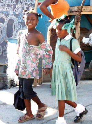 "In Haiti, a restavek child (on the left) walks to school, but never enters the doors. She is simply escorting the uniformed girl to school as part of her domestic duties. She smiles at Jean-Robert Cadet, who was speaking to her and encouraging her to ask her ""host family"" about going to school, too."