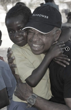 Cadet hugging a restavek in Haiti, where he returns regularly.