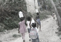 Restavek children carrying water