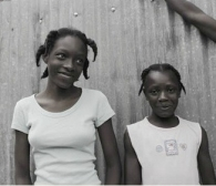 The girl on the right is a restavek who is abnormally short because of malnutrition.