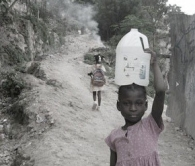 The restavek child carries water for the family while the other child goes to school.