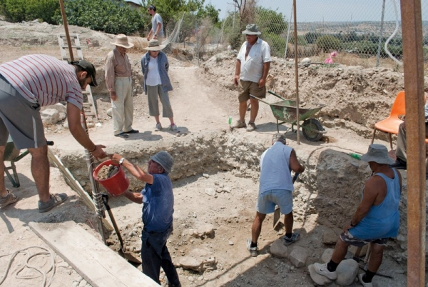 Local Cypriot workers excavate the site, while UC' Gisela Walberg observes. She is in the back, wearing a hat and standing next to the excavation's architect.