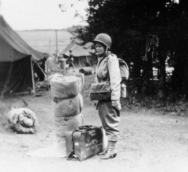"Beginning in May 1942, College of Medicine dean Stanley Dorst and colleagues selected physicians and nurses from the staff and graduates of the colleges of nursing and medicine to serve in the 25th. Here nurse Stella (last name unknown) prepares to leave England for France, ""complete with 18-inch bedroll and helmet,"" as Ashbaugh described."