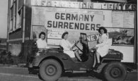 "Nurses sitting in a jeep with a large sign behind them that reads: ""Germany Surrenders."""